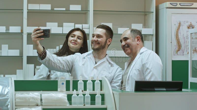 Η εύθυμη ομάδα του φαρμακοποιού και οι οικότροφοι παίρνουν selfie μέσω του smartphone στον εργασιακό χώρο στοκ φωτογραφία