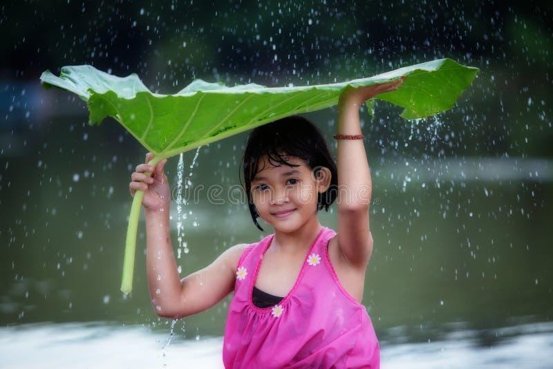 Η εύθυμη παίζοντας βροχή μικρών κοριτσιών στοκ φωτογραφία