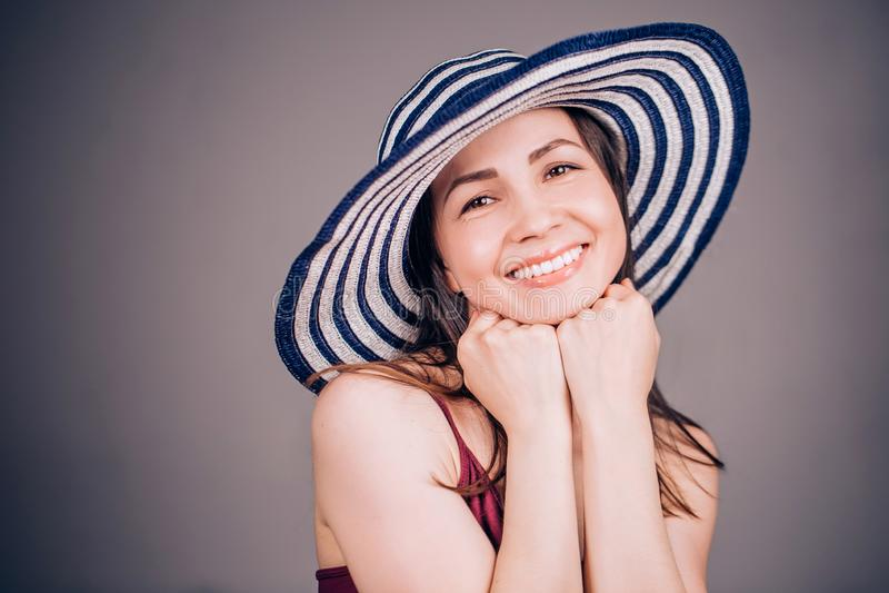 Η εύθυμη χαμογελώντας γυναίκα που φορά το ριγωτό καπέλο και το χέρι κρατά στο πηγούνι στοκ εικόνες