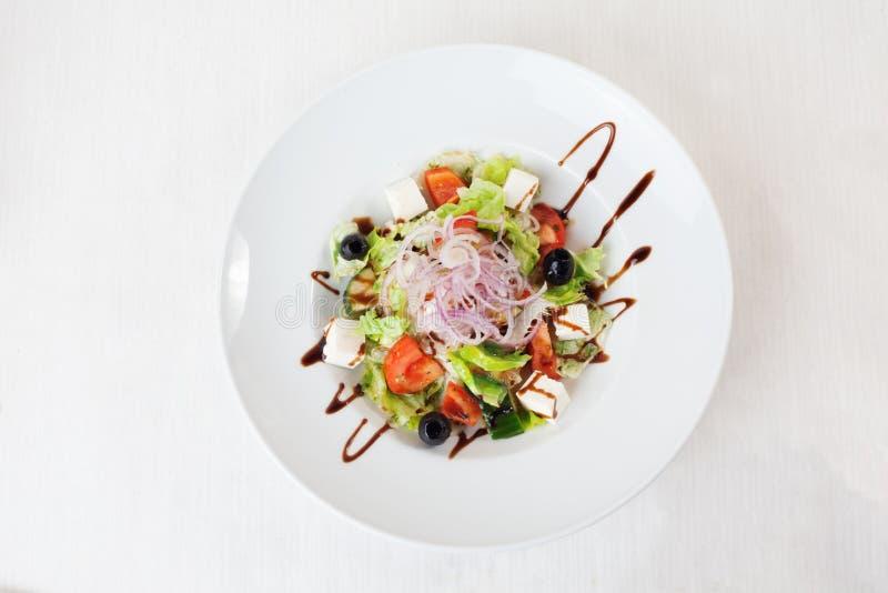 Η ελληνική σαλάτα με τη βαλσαμική σάλτσα μαρουλιού αγγουριών ντοματών ελιών στην κορυφή απομόνωσε το άσπρο υπόβαθρο στοκ φωτογραφίες