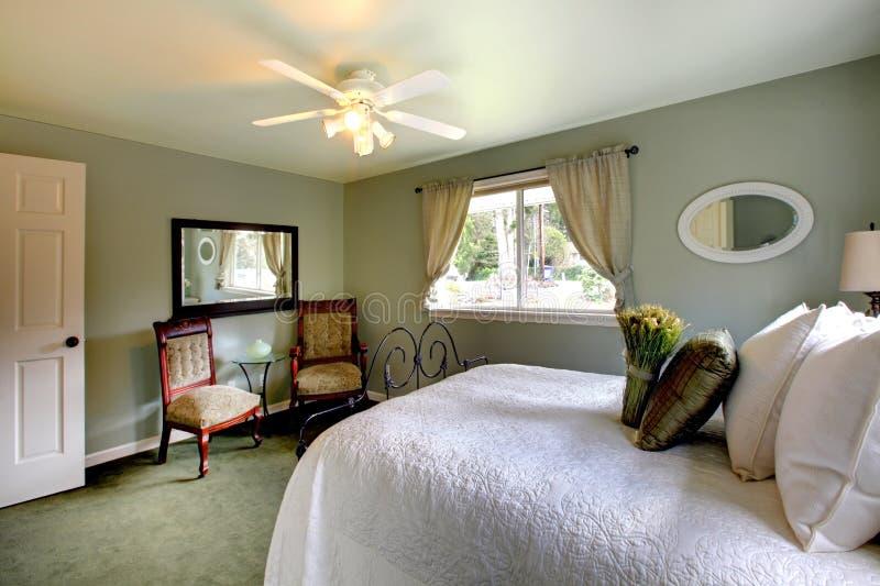 Η ελιά τονίζει την κρεβατοκάμαρα με το παλαιό κρεβάτι πλαισίων σιδήρου στοκ εικόνα
