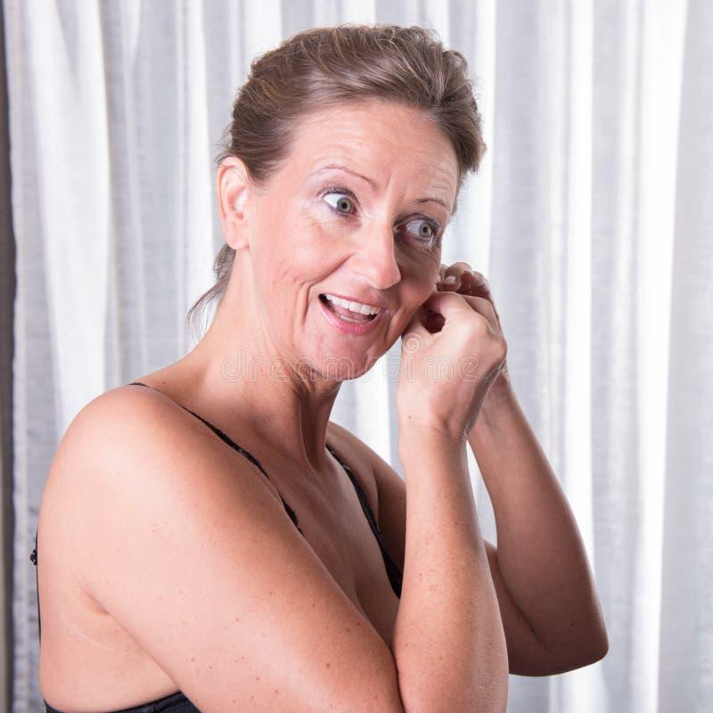 Η ελκυστική γυναίκα βάζει το σκουλαρίκι επάνω στοκ φωτογραφίες