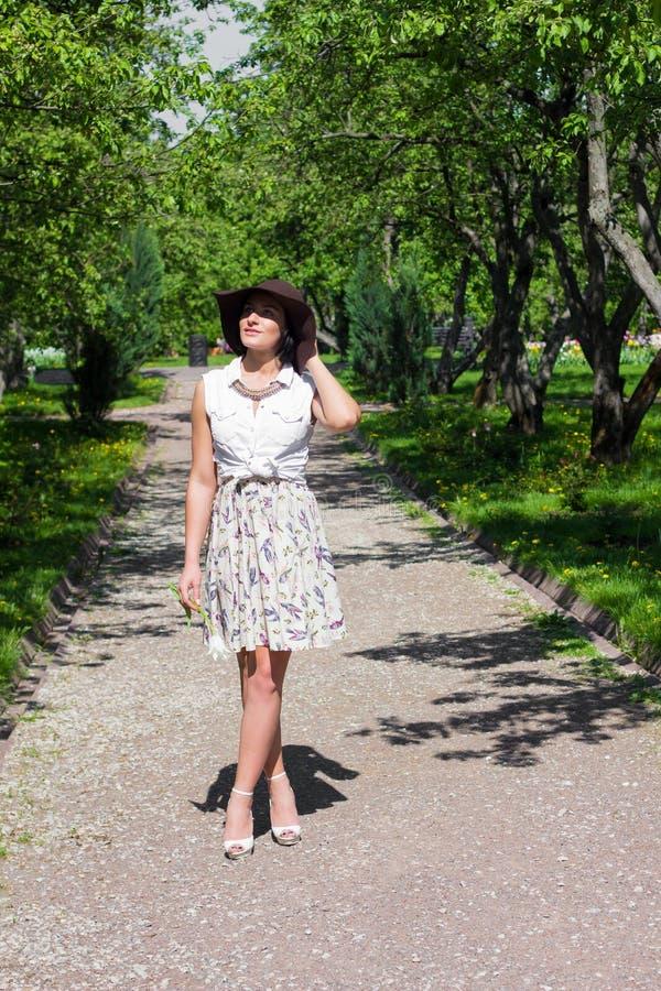 Η ελκυστική γυναίκα με ένα καπέλο περπατά στο πάρκο μια ηλιόλουστη ημέρα στοκ φωτογραφία με δικαίωμα ελεύθερης χρήσης