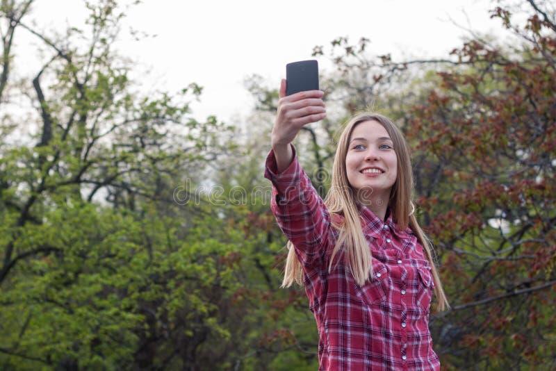 Η ελκυστική γυναίκα στο πάρκο κάνει selfie στοκ φωτογραφίες με δικαίωμα ελεύθερης χρήσης