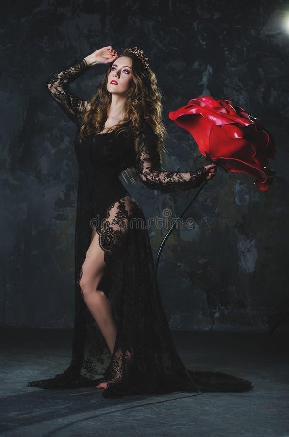 Η ελκυστική νέα γυναίκα σε ένα μακρύ μαύρο φόρεμα με πολύ έναν μεγάλο αυξήθηκε σε ένα υπόβαθρο τοίχων grunge στοκ εικόνες