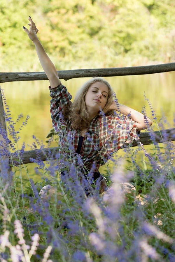 Η ελκυστική νέα γυναίκα χαλαρώνει στη χλόη και το τεντώνοντας χ στοκ εικόνα με δικαίωμα ελεύθερης χρήσης