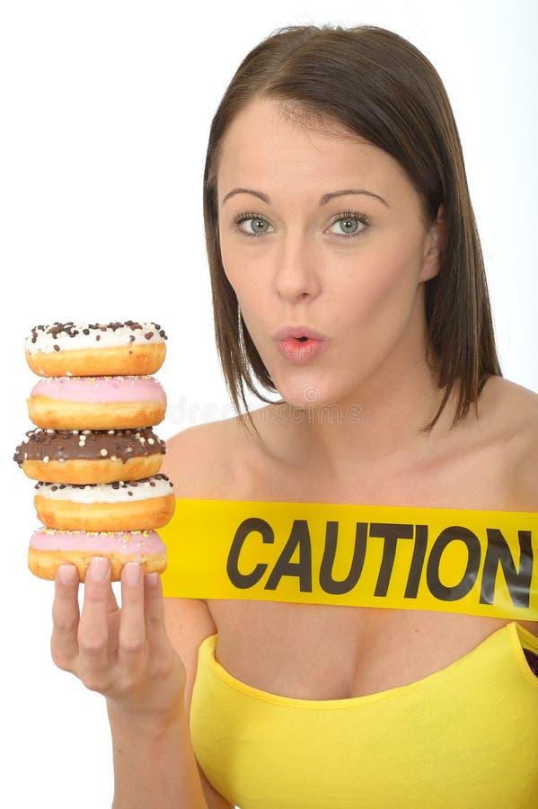 Η ελκυστική φυσική νέα γυναίκα που κρατά έναν σωρό παγωμένου Donuts υπογράφει με σύνεση στοκ φωτογραφίες