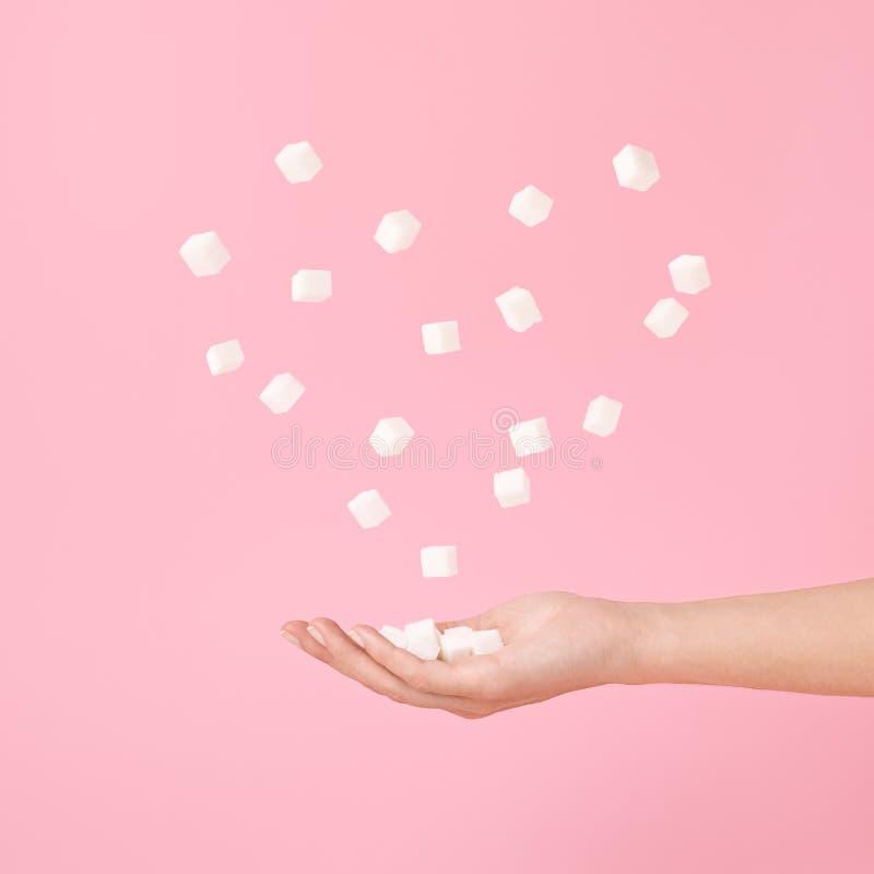 Η ζάχαρη κυβίζει υπό εξέταση και πετώντας κύβοι ζάχαρης στη μορφή καρδιών στο ροζ κρητιδογραφιών στοκ εικόνες