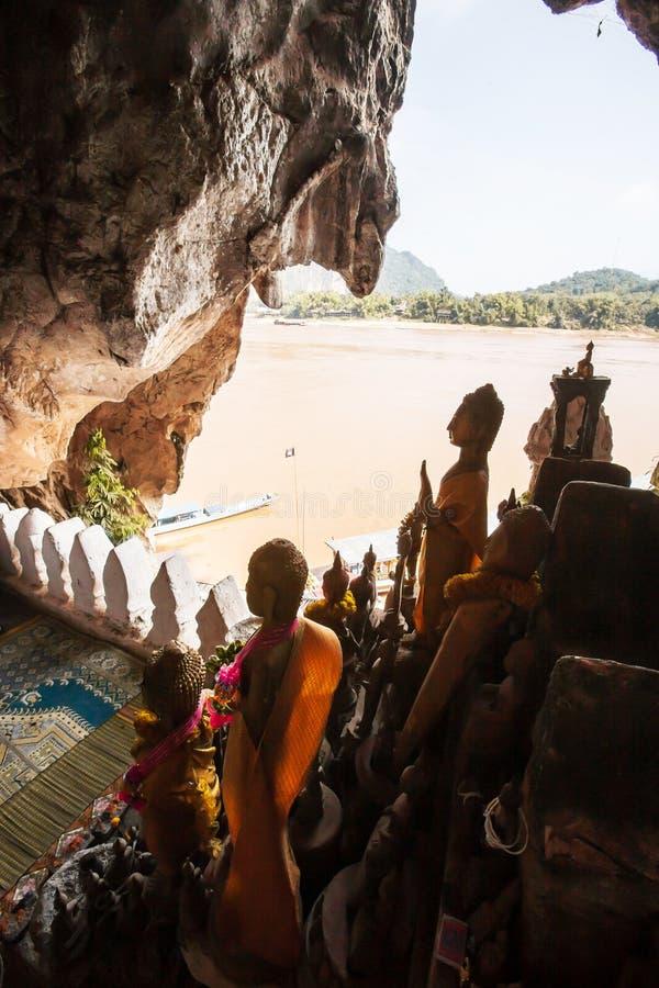 Η ζαλίζοντας άποψη στις σπηλιές OU Pak, διάσημες σπηλιές στον απότομο βράχο ασβεστόλιθων είναι γεμισμένη εικόνα του Βούδα μυριάδα στοκ φωτογραφία με δικαίωμα ελεύθερης χρήσης