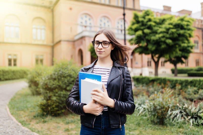 Η ζωή σπουδαστών αρχίζει Νέος έξυπνος θηλυκός φοιτητής πανεπιστημίου στην πανεπιστημιούπολη υπαίθρια στοκ εικόνα με δικαίωμα ελεύθερης χρήσης