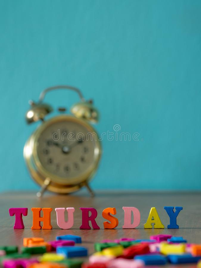 Η ζωηρόχρωμη ξύλινη ΠΕΜΠΤΗ λέξης στον ξύλινο πίνακα και το εκλεκτής ποιότητας ξυπνητήρι και το υπόβαθρο είναι μπλε σκονών Αγγλικό στοκ φωτογραφία με δικαίωμα ελεύθερης χρήσης