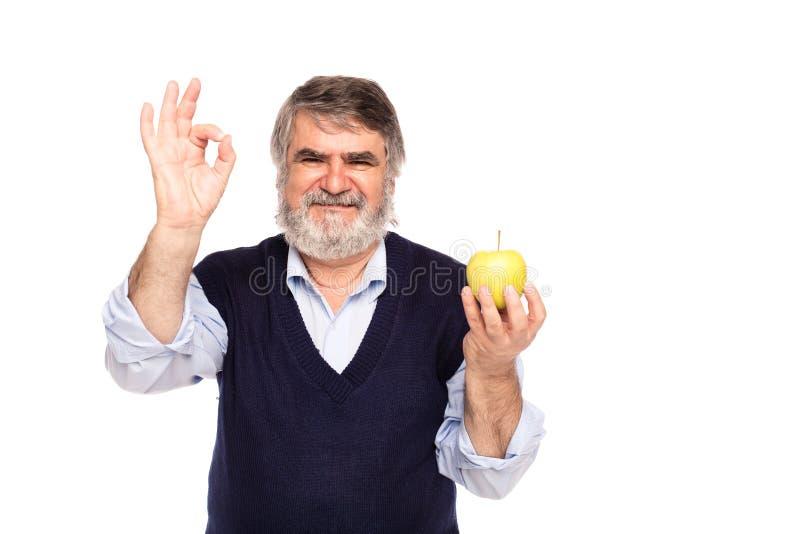 Ηληκιωμένος με το μήλο στα χέρια στοκ φωτογραφία