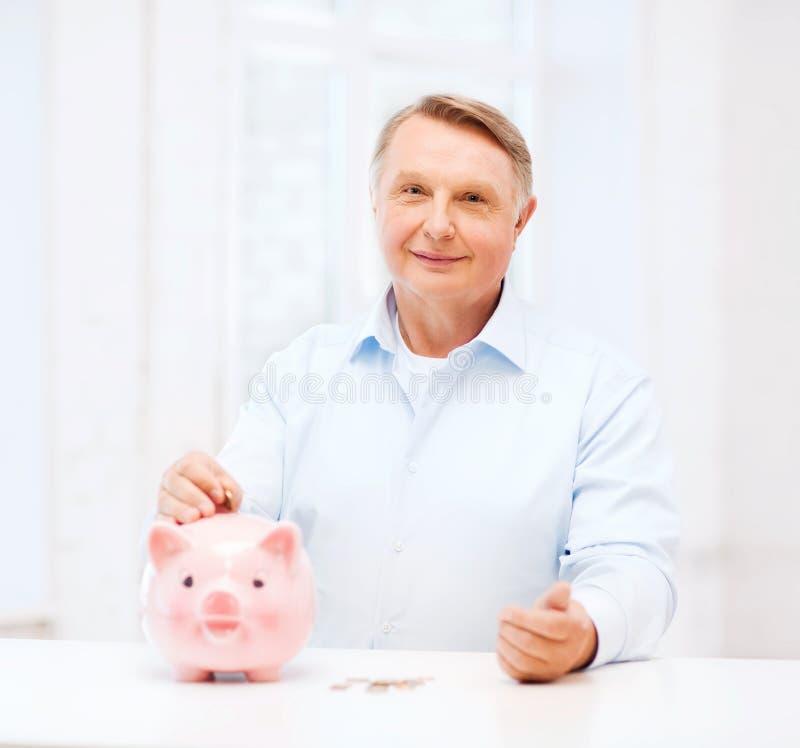 Ηληκιωμένος που βάζει το νόμισμα στη μεγάλη piggy τράπεζα στοκ εικόνες με δικαίωμα ελεύθερης χρήσης