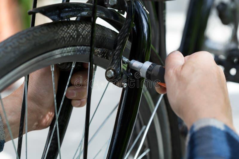 Ηληκιωμένος που επισκευάζει μια ρόδα ποδηλάτων στοκ εικόνες