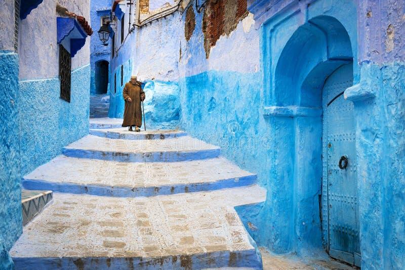 Ηληκιωμένος που περπατά σε μια οδό της πόλης Chefchaouen στο Μαρόκο στοκ εικόνα