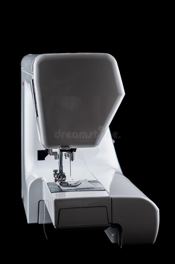 Η ηλεκτρομηχανική σύγχρονη άσπρη πλαστική πλάγια όψη μηχανών ραψίματος σχετικά με ένα μαύρο υπόβαθρο, απομονώνει στοκ εικόνα