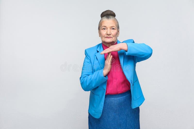 Η ηλικίας γυναίκα που παρουσιάζει χρόνο υπογράφει έξω στοκ εικόνα