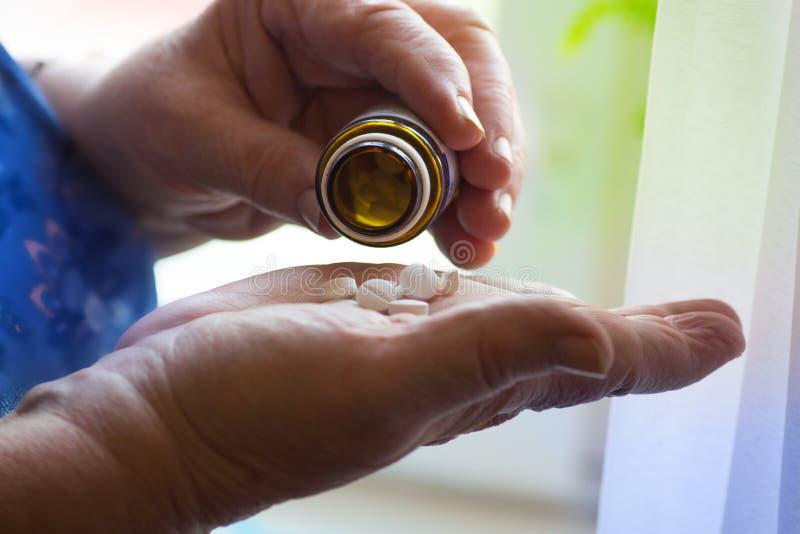 Η ηλικιωμένη γυναίκα βάζει το φάρμακο χαπιών στο χέρι της που απομονώνεται σε ένα άσπρο υπόβαθρο, ανώτερο φάρμακο χεριών στοκ φωτογραφία