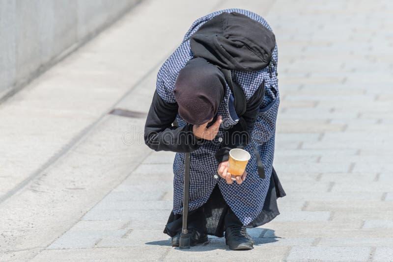 Η ηλικιωμένη γυναίκα επαιτών έκαμψε σε μια για τους πεζούς ζώνη, Γερμανία στοκ φωτογραφία με δικαίωμα ελεύθερης χρήσης