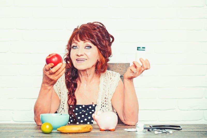 Η ηλικιωμένη γυναίκα επιλέγει το μπουκάλι μήλων ή χαπιών στοκ εικόνες