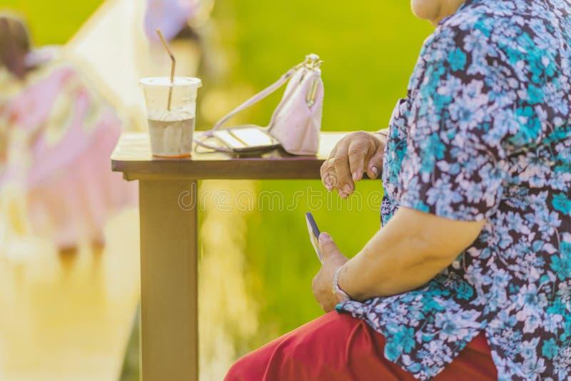 Η ηλικιωμένη γυναίκα κάθεται για τη στήριξη και την αναμονή το χρόνο να ληφθούν οι φωτογραφίες του ηλιοβασιλέματος στο μπαλκόνι τ στοκ εικόνες με δικαίωμα ελεύθερης χρήσης