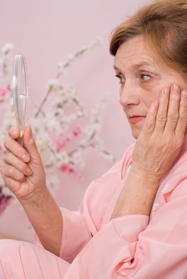 Η ηλικιωμένη γυναίκα κοιτάζει στον καθρέφτη στοκ εικόνα με δικαίωμα ελεύθερης χρήσης