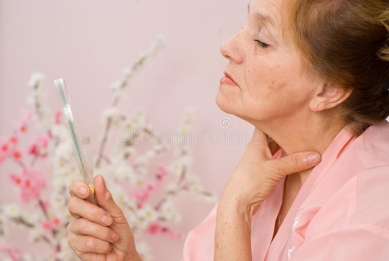 Η ηλικιωμένη γυναίκα κοιτάζει στον καθρέφτη στοκ φωτογραφίες