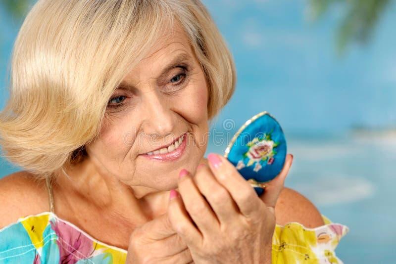 Η ηλικιωμένη γυναίκα κοιτάζει στον καθρέφτη στοκ φωτογραφία με δικαίωμα ελεύθερης χρήσης