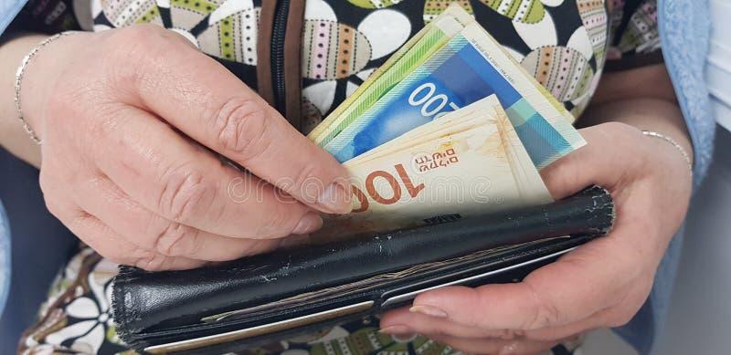 Η ηλικιωμένη γυναίκα κρατά στα χέρια τα ισραηλινά χρήματα μετρητών στοκ φωτογραφίες