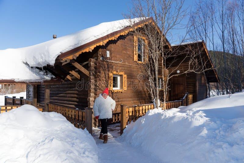Η ηλικιωμένη γυναίκα στέκεται κοντά στην είσοδο σε ένα ξύλινο σπίτι, ανάμεσα snowdrifts μια ηλιόλουστη χειμερινή ημέρα στοκ εικόνες
