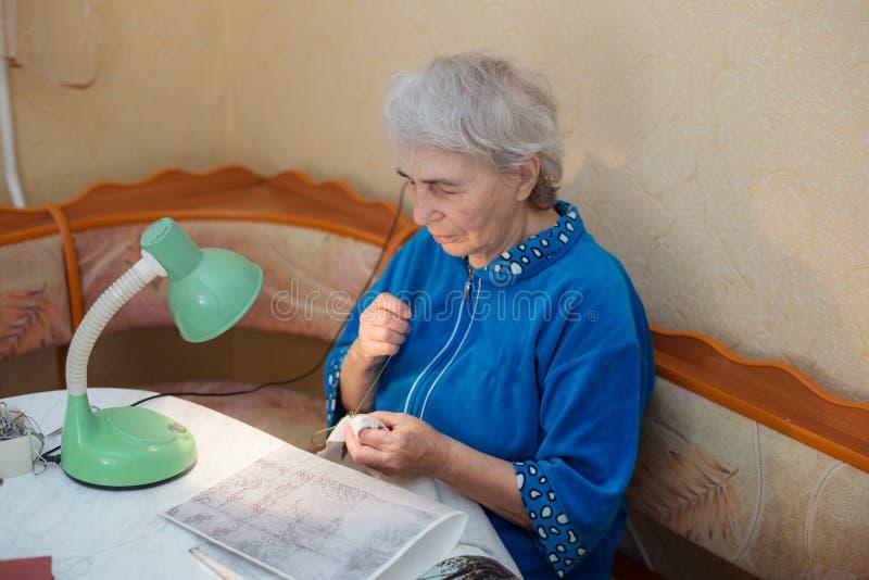 Η ηλικιωμένη γυναίκα συμμετέχει στην κεντητική στοκ φωτογραφία