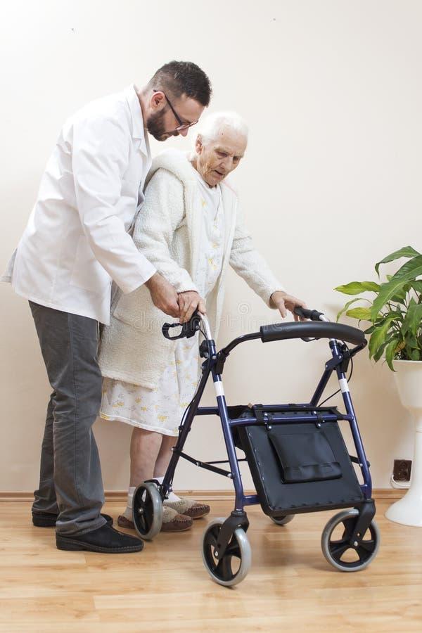 Η ηλικιωμένη κυρία μαθαίνει να περπατά με τη βοήθεια ενός μπαλκονιού αποκατάστασης ενός γιατρού στοκ φωτογραφία με δικαίωμα ελεύθερης χρήσης