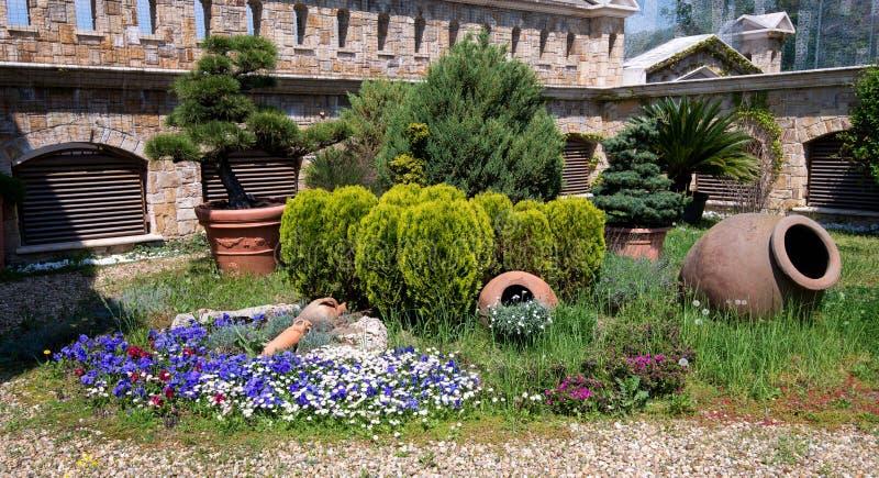 Η ηλιόλουστη ημέρα σε έναν κήπο άνοιξη με τα δοχεία, τα δέντρα, τους Μπους και την άνθηση αργίλου ανθίζει την έννοια του τρόπου ζ στοκ φωτογραφίες