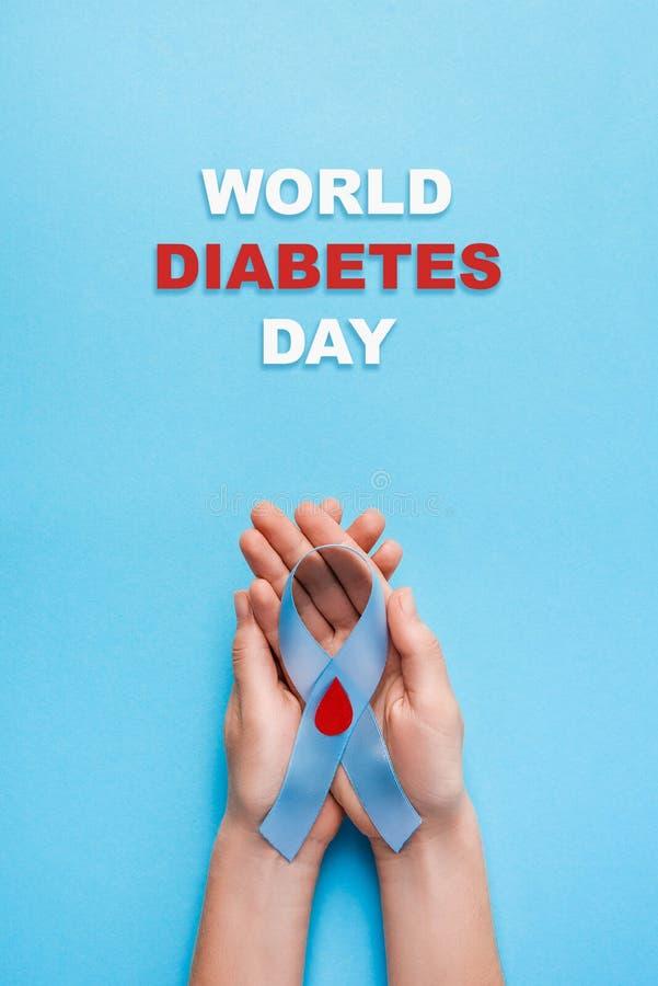 Η ημέρα παγκόσμιου διαβήτη επιγραφής και η μπλε συνειδητοποίηση κορδελλών με το κόκκινο αίμα μειώνονται στα χέρια γυναικών σε ένα στοκ εικόνες