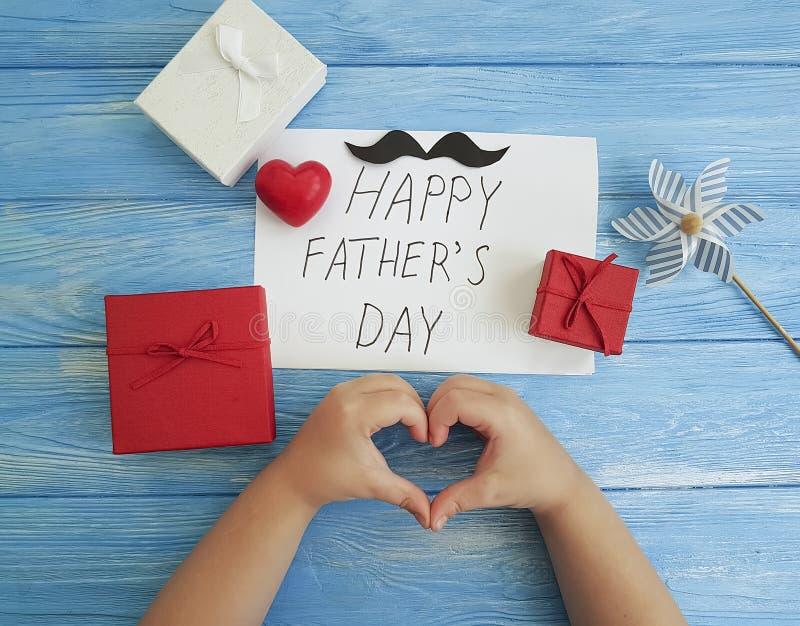 Η ημέρα πατέρων ` s, χέρια μωρών ` s, γιορτάζει την κόκκινη καρδιά συγχαρητηρίων σε ένα μπλε ξύλινο υπόβαθρο στοκ φωτογραφία με δικαίωμα ελεύθερης χρήσης