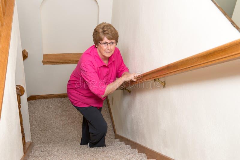Η ηλικιωμένη γυναίκα αναρριχείται στα ζητήματα κινητικότητας σκαλοπατιών στοκ φωτογραφίες