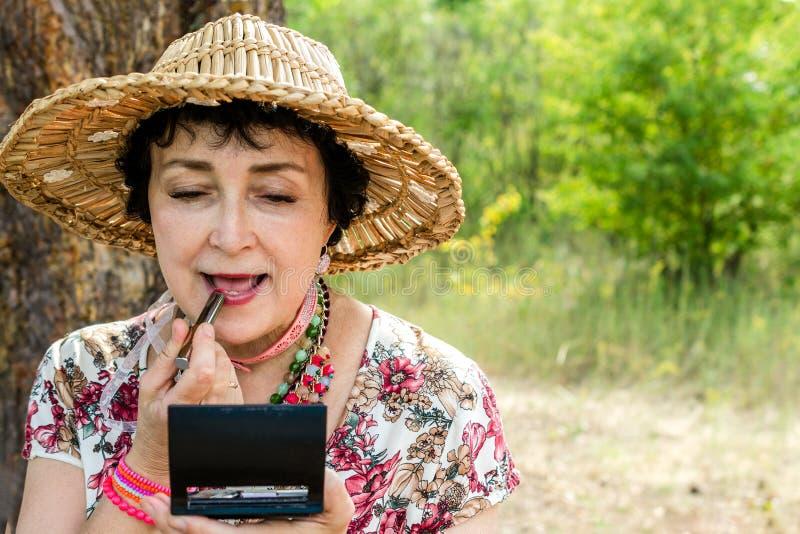 Η ηλικιωμένη γυναίκα που φορά ένα καπέλο αχύρου, χρησιμοποιεί το κραγιόν της στη φύση στοκ φωτογραφία