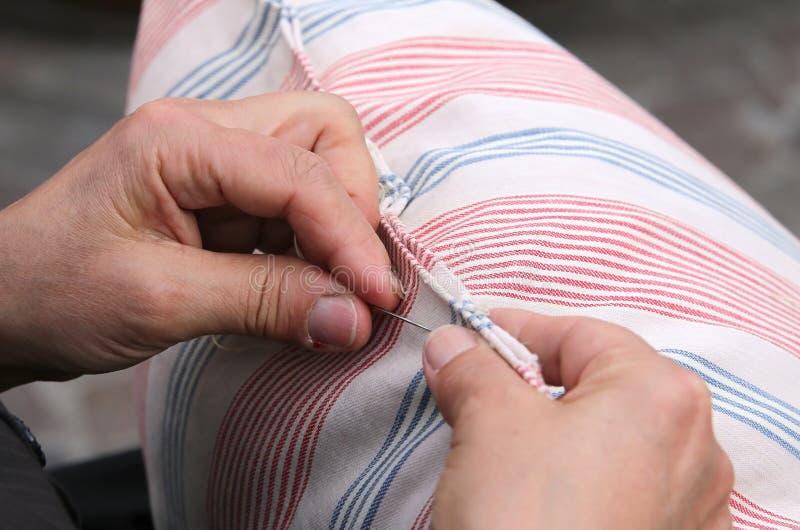 η ηλικιωμένη γυναίκα ράβοντας με τη βελόνα και περνά κλωστή στο μαξιλάρι στοκ εικόνες με δικαίωμα ελεύθερης χρήσης