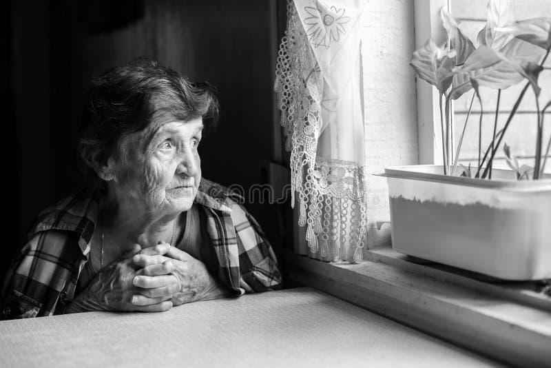 Η ηλικιωμένη γυναίκα φαίνεται μελαγχολικά έξω το παράθυρο στοκ εικόνες με δικαίωμα ελεύθερης χρήσης