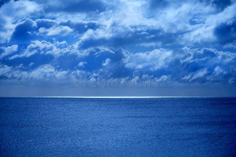 Η θάλασσα και ο ουρανός στο κατώτατο μισό είναι μια ήρεμη βαθιά μπλε θάλασσα, στον ορίζοντα είναι μια γραμμή άσπρου φωτός πυράκτω στοκ φωτογραφία