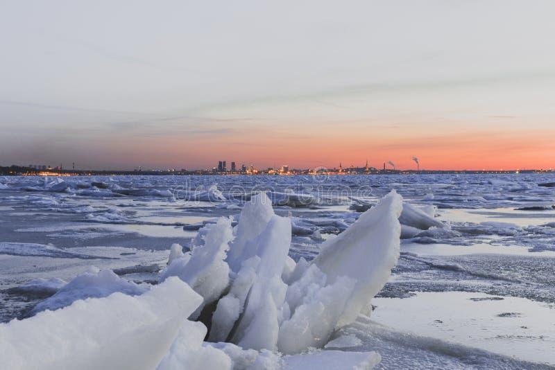 Η θάλασσα της Βαλτικής Icey με τον ορίζοντα του Ταλίν ` s πίσω από το κατά τη διάρκεια ενός ηλιοβασιλέματος στοκ φωτογραφίες