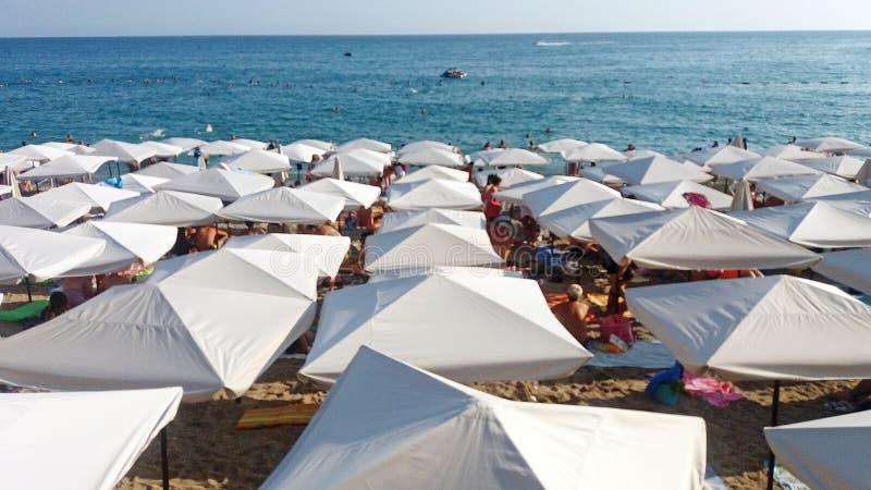 Η θάλασσα με τις άσπρες ομπρέλες παραλιών στοκ εικόνα με δικαίωμα ελεύθερης χρήσης