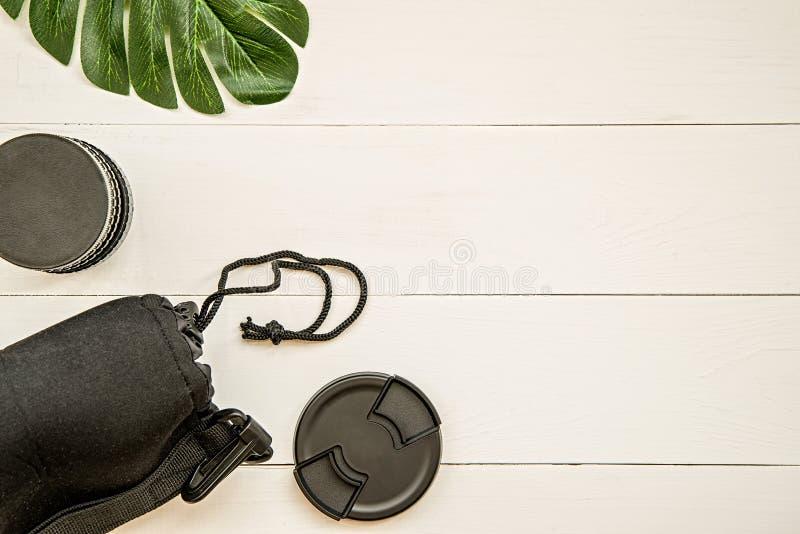 Η θέση εργασίας φωτογράφων με την κάλυψη φακών, ο μαύρος φακός, η περίπτωση και το τροπικό επίπεδο φύλλων βάζουν τη τοπ άποψη στοκ εικόνες