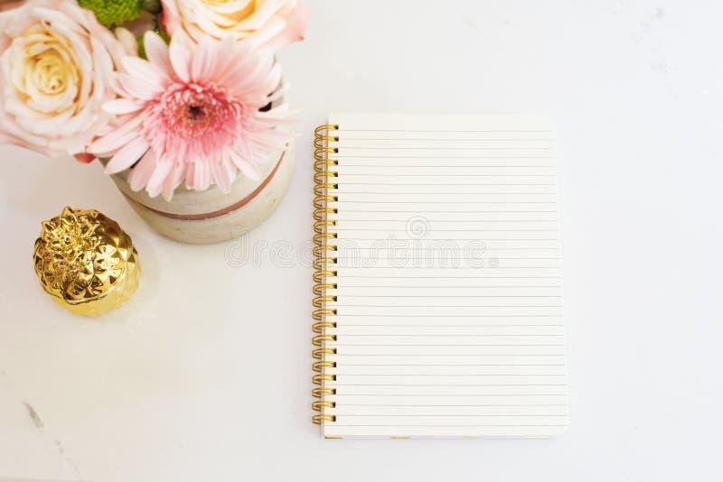 Η θηλυκή έννοια εργασιακών χώρων στο επίπεδο βάζει το ύφος με τα λουλούδια, χρυσός ανανάς, σημειωματάριο στο άσπρο μαρμάρινο υπόβ στοκ εικόνα με δικαίωμα ελεύθερης χρήσης
