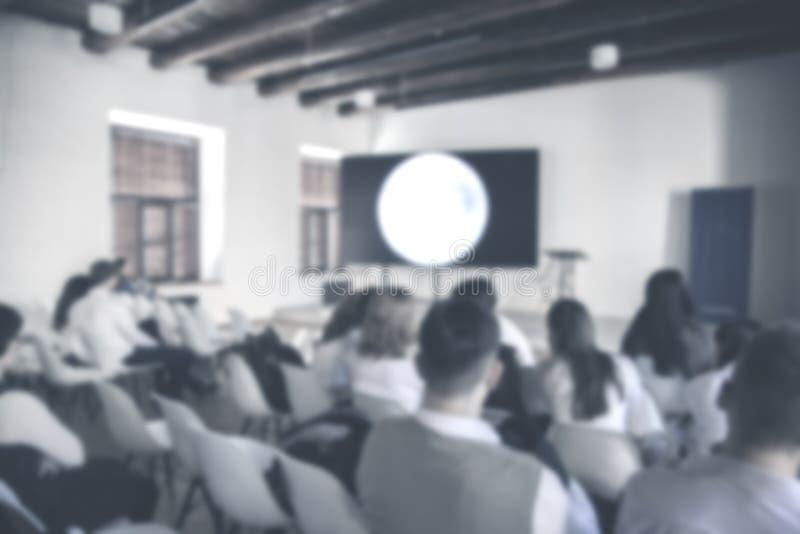 Η θολωμένη εικόνα της ομάδας παραγωγής κάθεται και στεμένος, ο πρόεδρος μιλά με το επιχειρησιακό πρόγραμμα στο τηλεοπτικό στούντι στοκ εικόνες με δικαίωμα ελεύθερης χρήσης