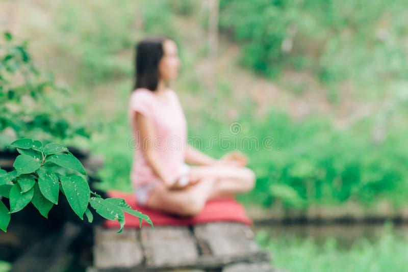 Η θολωμένη φωτογραφία μιας γυναίκας σε μια γιόγκα θέτει και περισυλλογή στη φύση στοκ εικόνες με δικαίωμα ελεύθερης χρήσης