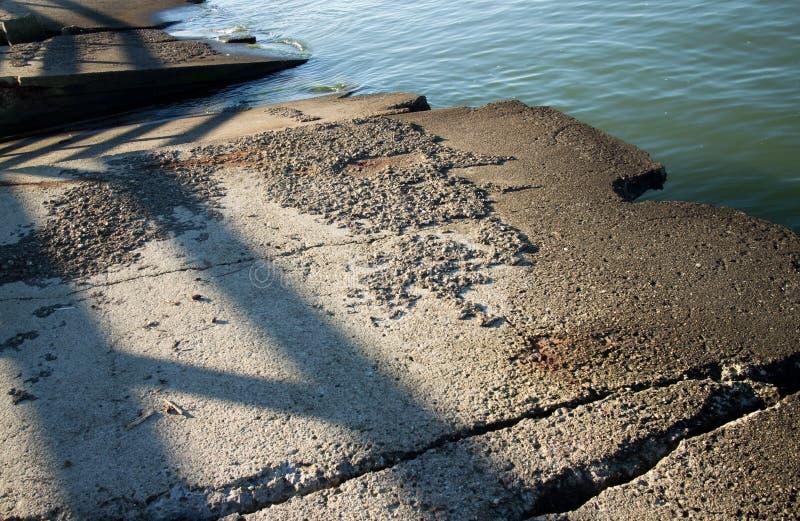 Η διαβρωμένη περίληψη ξεπέρασε τις τσιμεντένιες πλάκες στην άκρη ενός ήρεμου κόλπου κατά μήκος της αμερικανικής βορειοδυτικής ακτ στοκ εικόνα με δικαίωμα ελεύθερης χρήσης