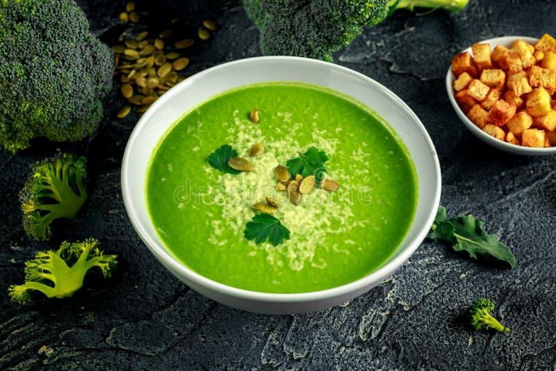 Η διαιτητική σούπα κρέμας μπρόκολου ομαλή με ψεκάζει των σπόρων ηλίανθων, των φύλλων μαϊντανού και croutons στον πίνακα πετρών στοκ εικόνες με δικαίωμα ελεύθερης χρήσης