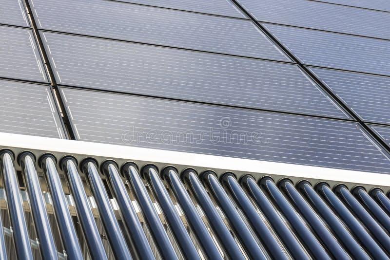 Ηλιακές θερμικές επίπεδες οθόνες με τους εκκενωθε'ντες συλλέκτες σωλήνων Πολλές επιχειρήσεις εγκαθιστούν τις ανανεωμένες πηγές εν στοκ εικόνες