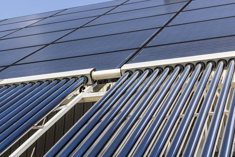 Ηλιακές θερμικές επίπεδες οθόνες με τους εκκενωθε'ντες συλλέκτες σωλήνων Πολλές επιχειρήσεις εγκαθιστούν τις ανανεωμένες πηγές εν στοκ φωτογραφίες με δικαίωμα ελεύθερης χρήσης